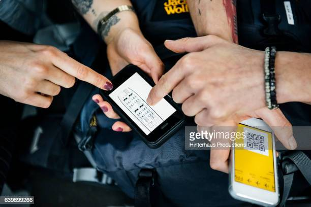 Hands of backpackers checking boarding passes on their smart phone