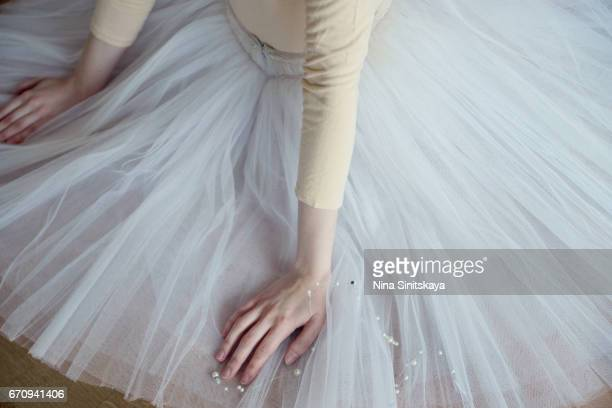 Hands of ballet dancer on the tulle skirt