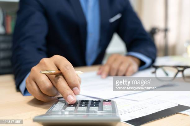 hands of bank officer calculating loans - bank manager stock pictures, royalty-free photos & images