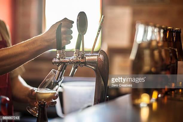 Hands of bartender pulling beer pump