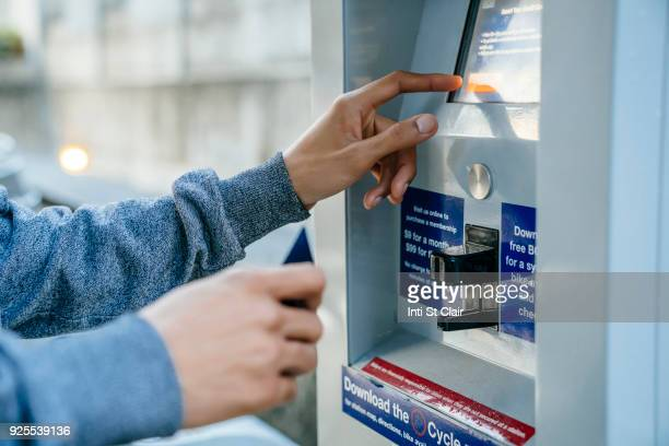 Hands of Black man paying at kiosk with credit card
