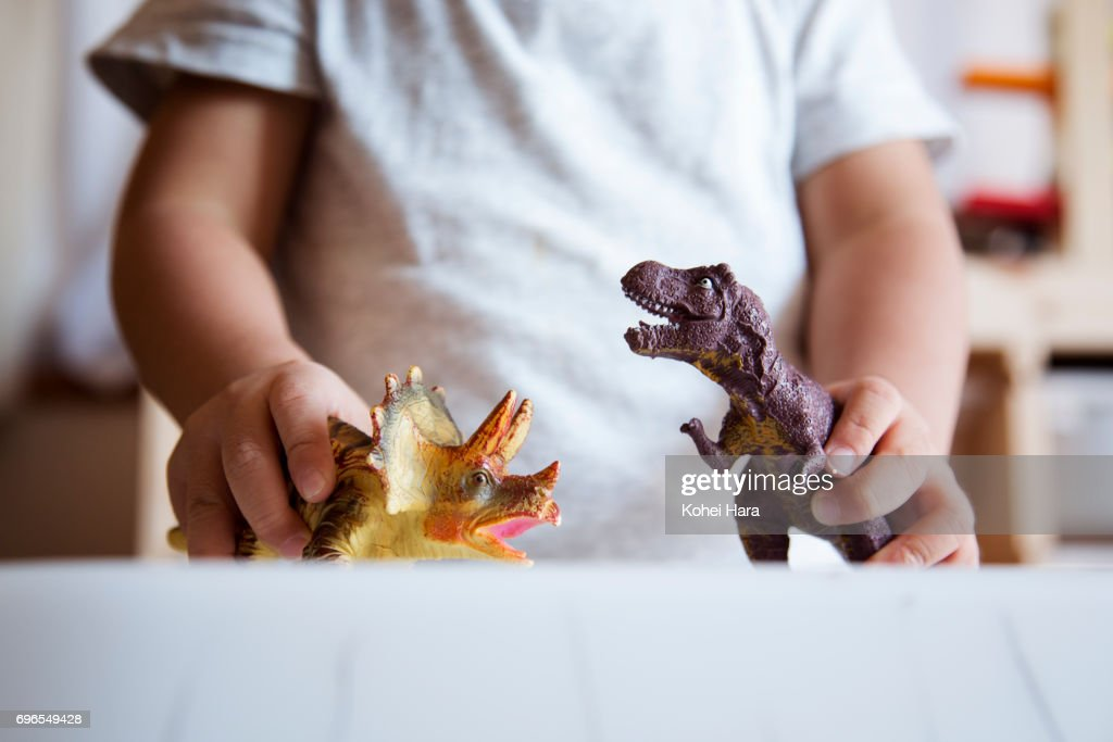 Hands of boy playing with miniature scale dinosaurs : ストックフォト
