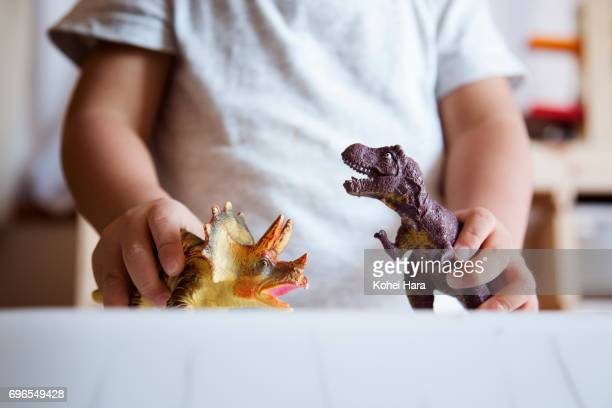 Hands of boy playing with miniature scale dinosaurs