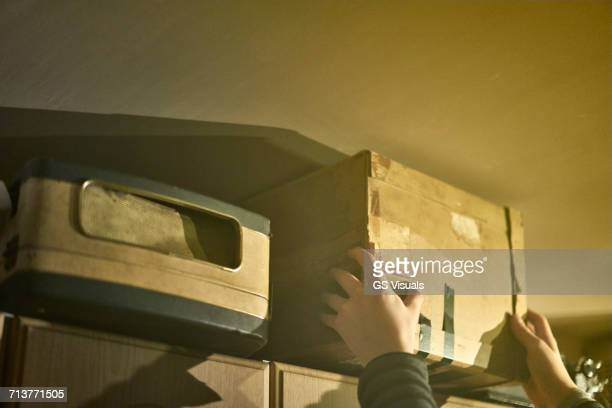 Hands of boy reaching to remove cardboard box from shelves