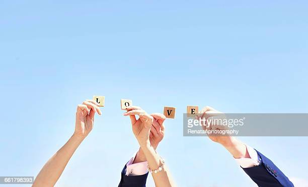 Hands of bride and groom holding up Alphabet letters spelling word love
