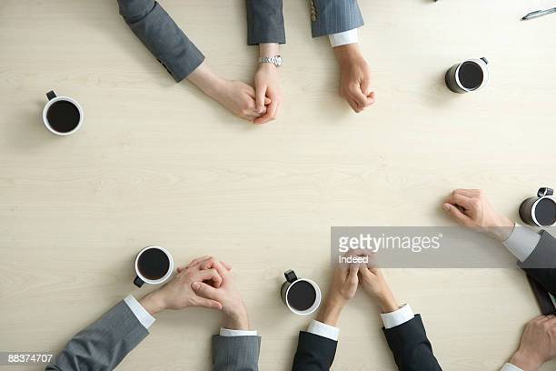 Hands of business people on meeting table