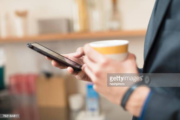 hands of businessman holding coffee cup and smartphone - heshphoto photos et images de collection