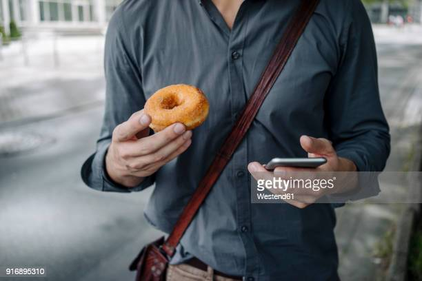 Hands of businessman holding doughnut and smartphone, Partial view