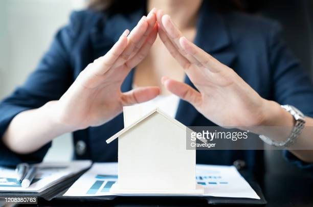 hands of businesswoman covering the wood house. property insurance and security concept. - - security_(finance) stock pictures, royalty-free photos & images