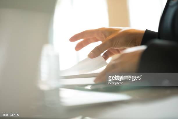 hands of businesswoman organising paperwork at office desk - heshphoto photos et images de collection