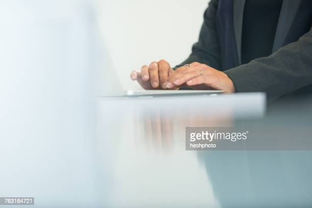 hands of businesswoman typing on laptop at office desk - heshphoto photos et images de collection