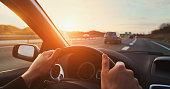 hands of car driver on steering wheel, road trip