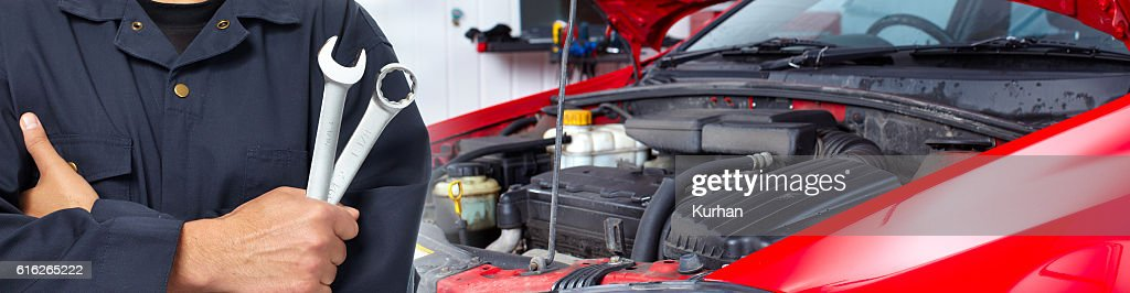 Hands of car mechanic with wrench in garage. : Stock Photo