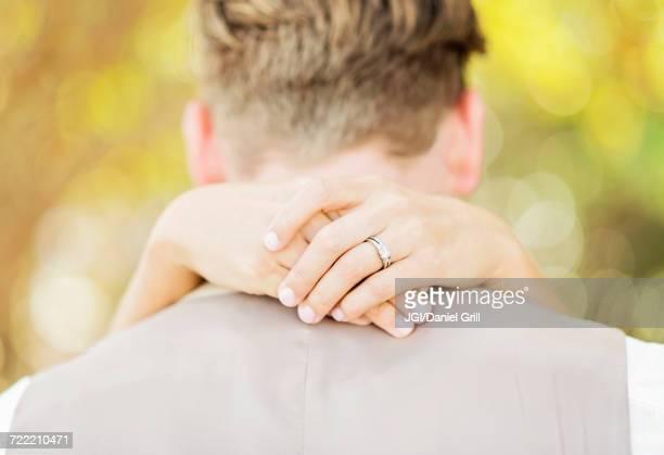 Hands of Caucasian bride hugging groom outdoors