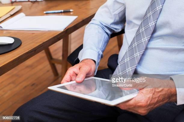Hands of Caucasian businessman holding digital tablet