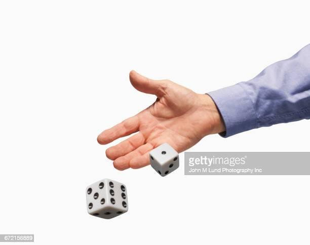 hands of caucasian businessman rolling dice on white background - dobbelsteen stockfoto's en -beelden
