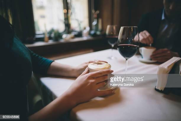 hands of caucasian couple drinking coffee and wine - koffie drank stockfoto's en -beelden