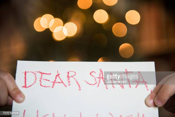 Hands of Caucasian girl holding dear Santa letter