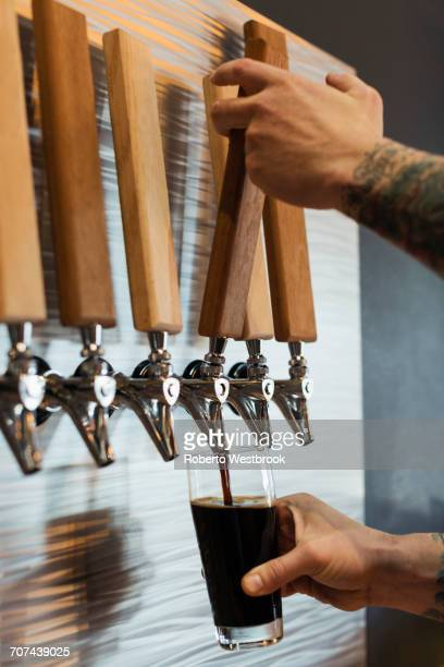 Hands of Caucasian man pouring beer from tap