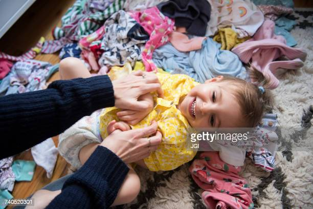 hands of caucasian mother tickling baby daughter on floor - diaper girl photos et images de collection
