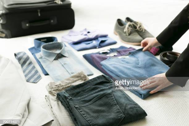 Hands of Caucasian woman arranging clothing for man on bed
