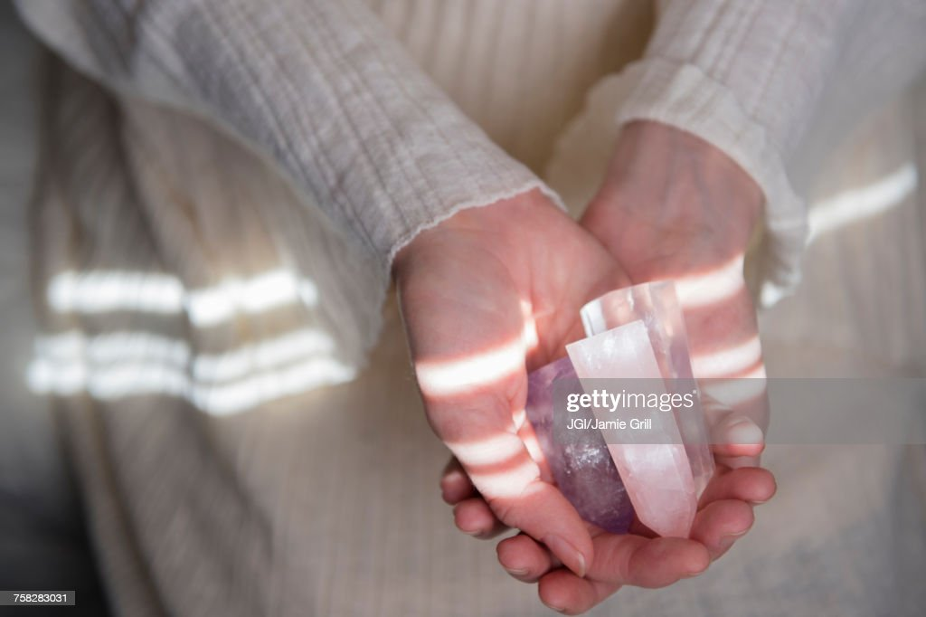 Hands of Caucasian woman holding crystals : Stock Photo