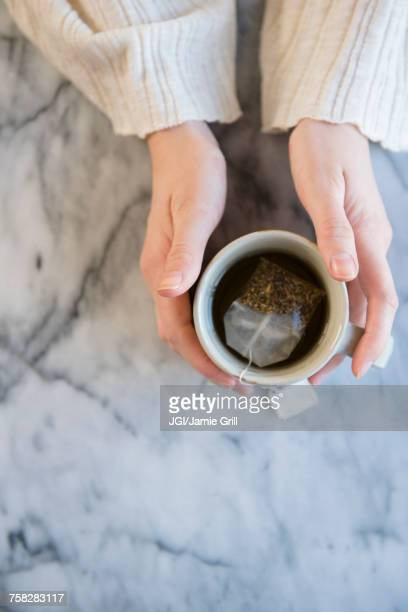 Hands of Caucasian woman holding cup of tea