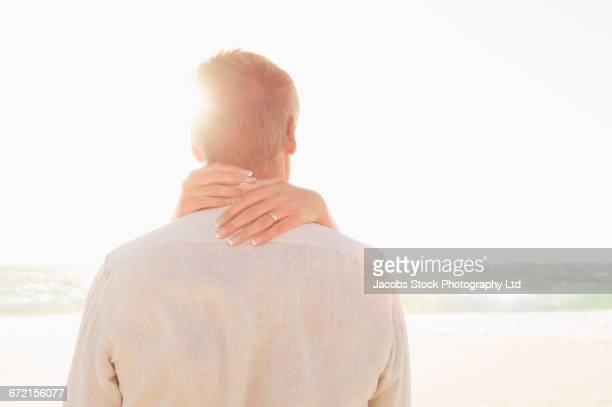 Hands of Caucasian woman hugging man at beach
