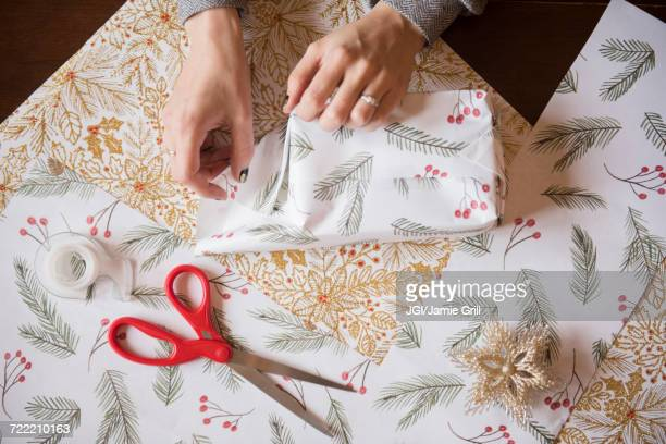 hands of caucasian woman wrapping christmas gifts - gift wrapping stock pictures, royalty-free photos & images