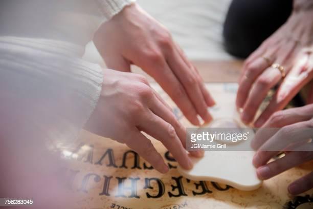 hands of caucasian women using a ouija board - ghost player foto e immagini stock