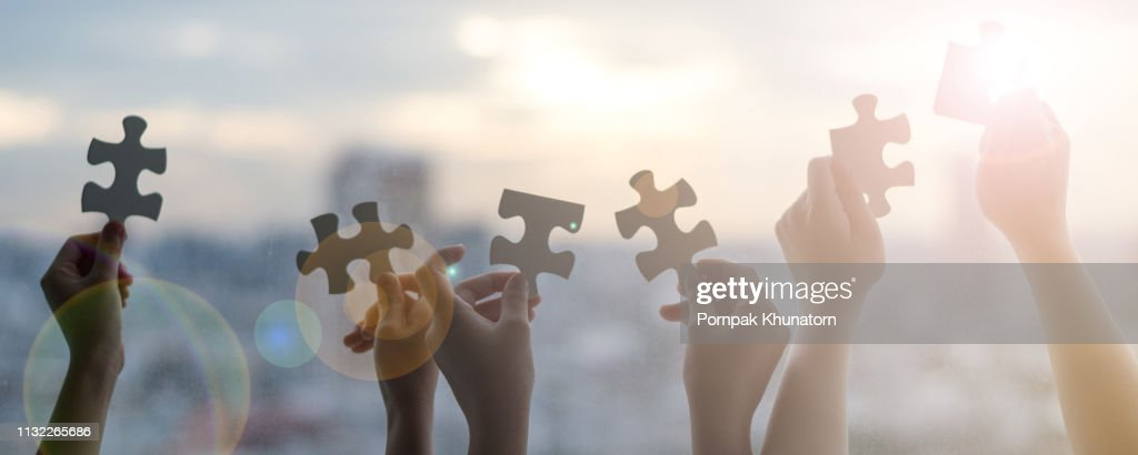 Hands of children students holding pieaces of jiwsaw together as a symbol for autism or teamwork in school. : Stock Photo