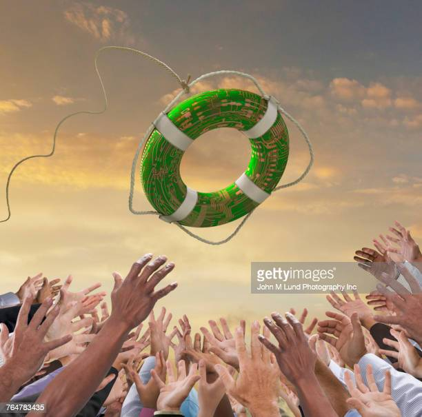 hands of crowd reaching for green life ring - bailout stock pictures, royalty-free photos & images
