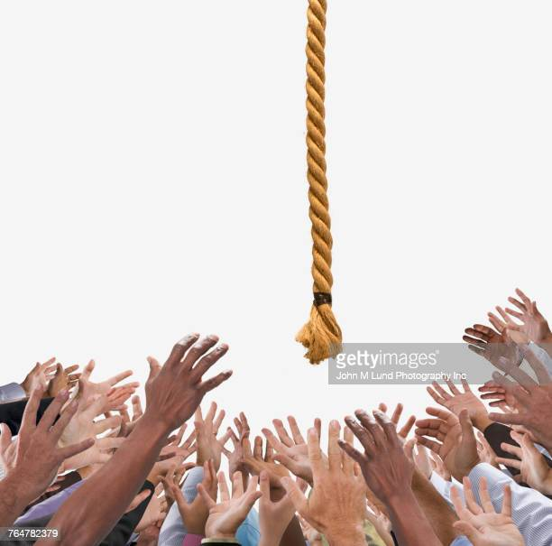 Hands of crowd reaching to rope in sky