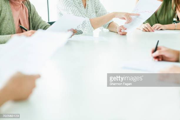Hands of decision makers at conference table