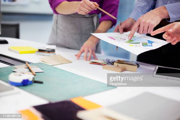 hands of designers pointing to layout at table - interior design foto e immagini stock