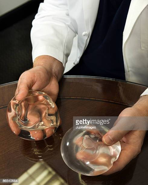 Hands of doctor holding breast implants