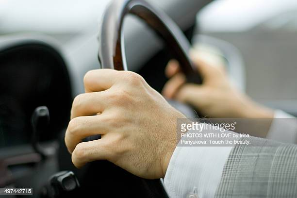 Hands of driver on steering wheel