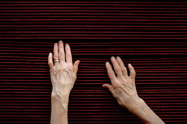 Hands of elderly lady touching red woolen threads