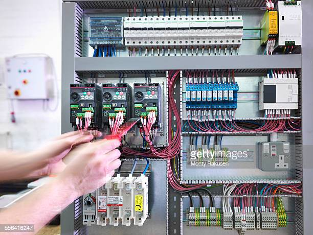 Hands of electrical engineer testing switch board in engineering factory
