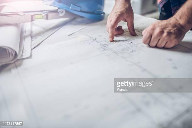 hände des ingenieurs, der an der blaupause arbeitet - lageplan stock-fotos und bilder