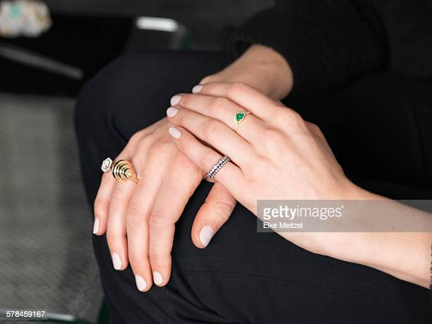 Hands of female jeweler wearing variety of rings in jewellery shop
