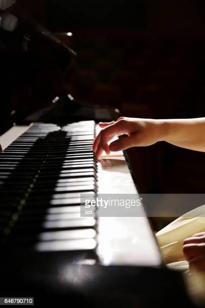 Hands of female pianist playing piano,close up