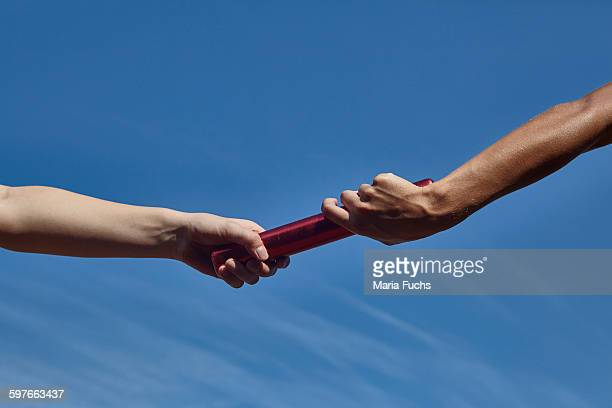 Hands of female relay runners passing baton against blue sky