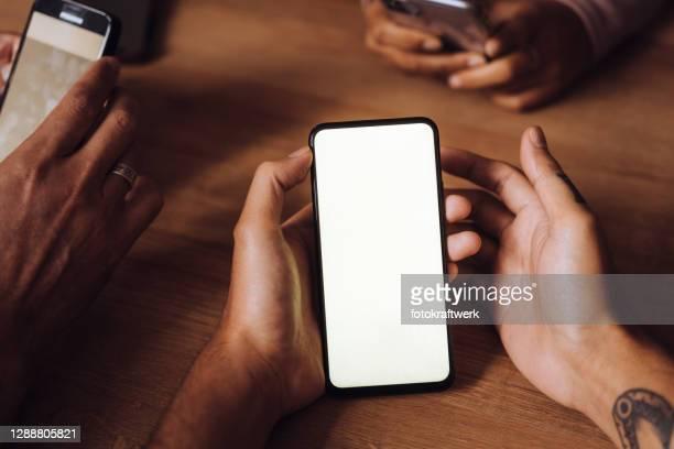 handen van vrienden die mobiele telefoons op lijst in restaurant in weekend gebruiken - black hand holding phone stockfoto's en -beelden