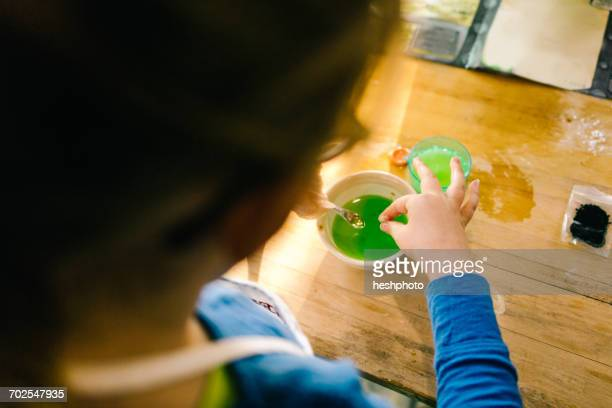 hands of girls doing science experiment, with green liquid - heshphoto imagens e fotografias de stock