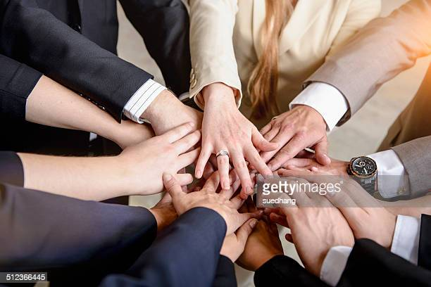 Hands of group of businesswomen and men together in a circle