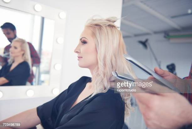 Hands of hairdresser holding hair straighteners for model at photo shoot