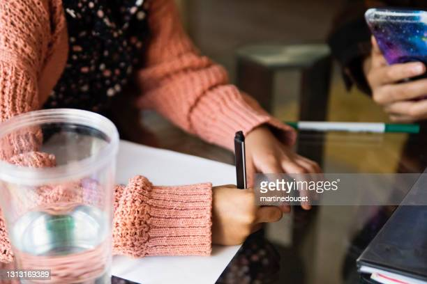 """hands of ittle girl homeschooling on the dining room table. - """"martine doucet"""" or martinedoucet stock pictures, royalty-free photos & images"""