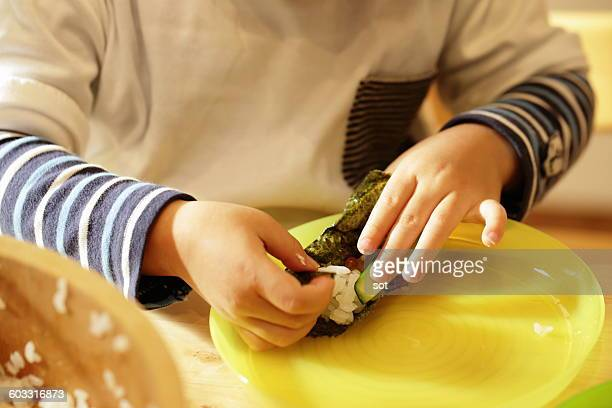 Hands of little boy making Hand Roll Sushi