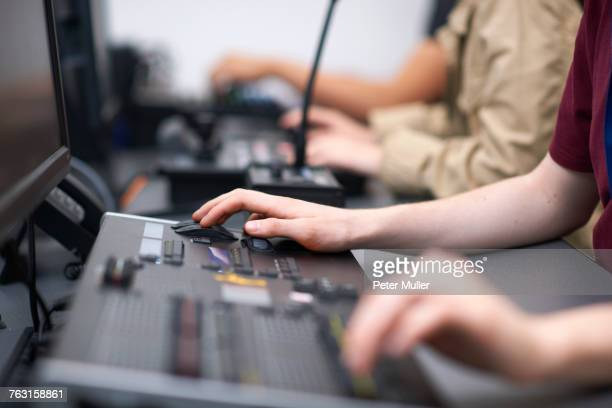 hands of male and female college students at mixing desk in tv studio - post-production stock pictures, royalty-free photos & images
